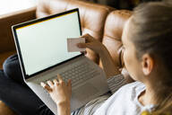 Young woman on couch at home shopping online - GIOF06723