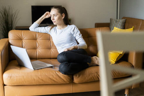 Young woman sitting on couch at home with laptop - GIOF06726