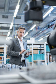 Businessman with tablet in a modern factory hall looking at robot - DIGF07212