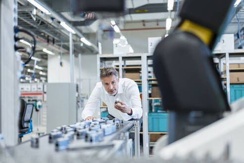 Businessman in a modern factory hall examiming workpieces - DIGF07218