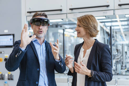 Businessman with AR glasses and businesswoman in a modern factory - DIGF07242