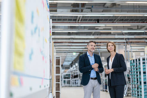 Businessman and businesswoman talking in a factory hall - DIGF07269