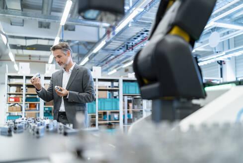 Businessman examining workpieces in a modern factory hall - DIGF07308