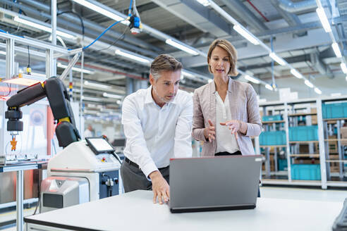 Businessman and businesswoman with laptop talking in a modern factory hall - DIGF07341