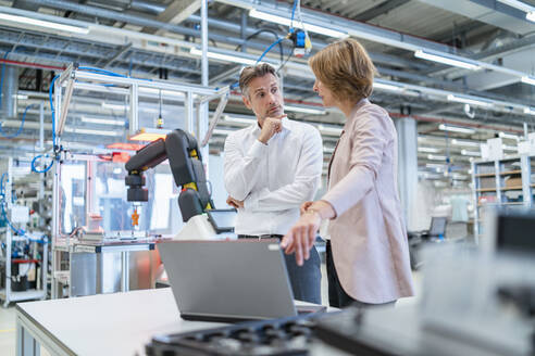 Businessman and businesswoman with laptop talking in a modern factory hall - DIGF07344