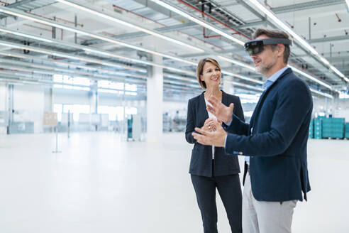 Businessman with AR glasses and businesswoman in a factory hall - DIGF07359