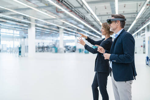 Businessman with AR glasses and businesswoman in a factory hall - DIGF07362
