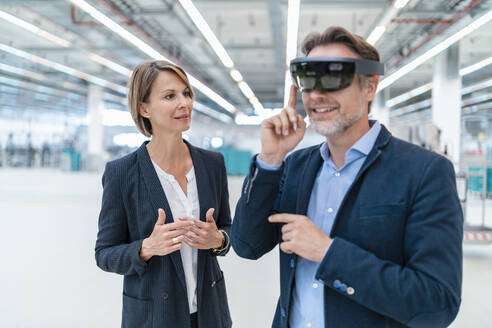 Businessman with AR glasses and businesswoman in a factory hall - DIGF07365