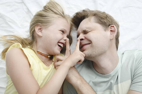 Russia, Sochi, Father and smiling daughter in the bedroom - EYAF00283