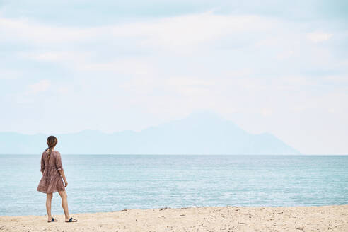 Young woman with summer dress looking at mount Athos, Greece. - BZF00492