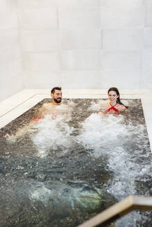 Man and woman enjoying the whirlpool in a spa - LJF00403