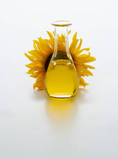 Sunflower oil in carafe with sunflower blossom. Isolated on white - PPXF00217