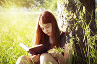 Girl leaning against tree trunk reading a book - LVF08161