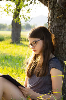 Girl leaning against tree trunk reading a book in nature - LVF08164