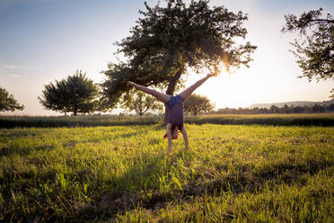 Teenage girl doing handstand in grassy field at sunset - LVF08165