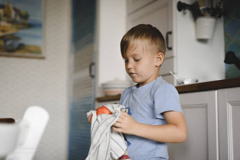 Russia, Moscow, boy with peach in the kitchen - EYAF00296