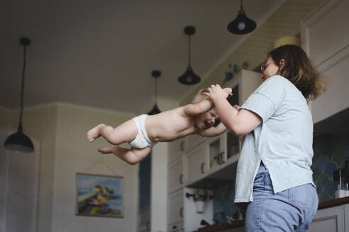 Russia, Moscow, cute smiling little boy playing with his mother in the kitchen - EYAF00299