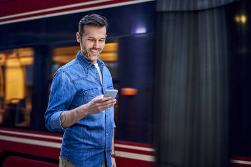 Man using smartphone while standing in the city with tram in background - BSZF01080