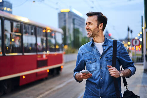 Man using smartphone while waiting for public tram in the evening - BSZF01083