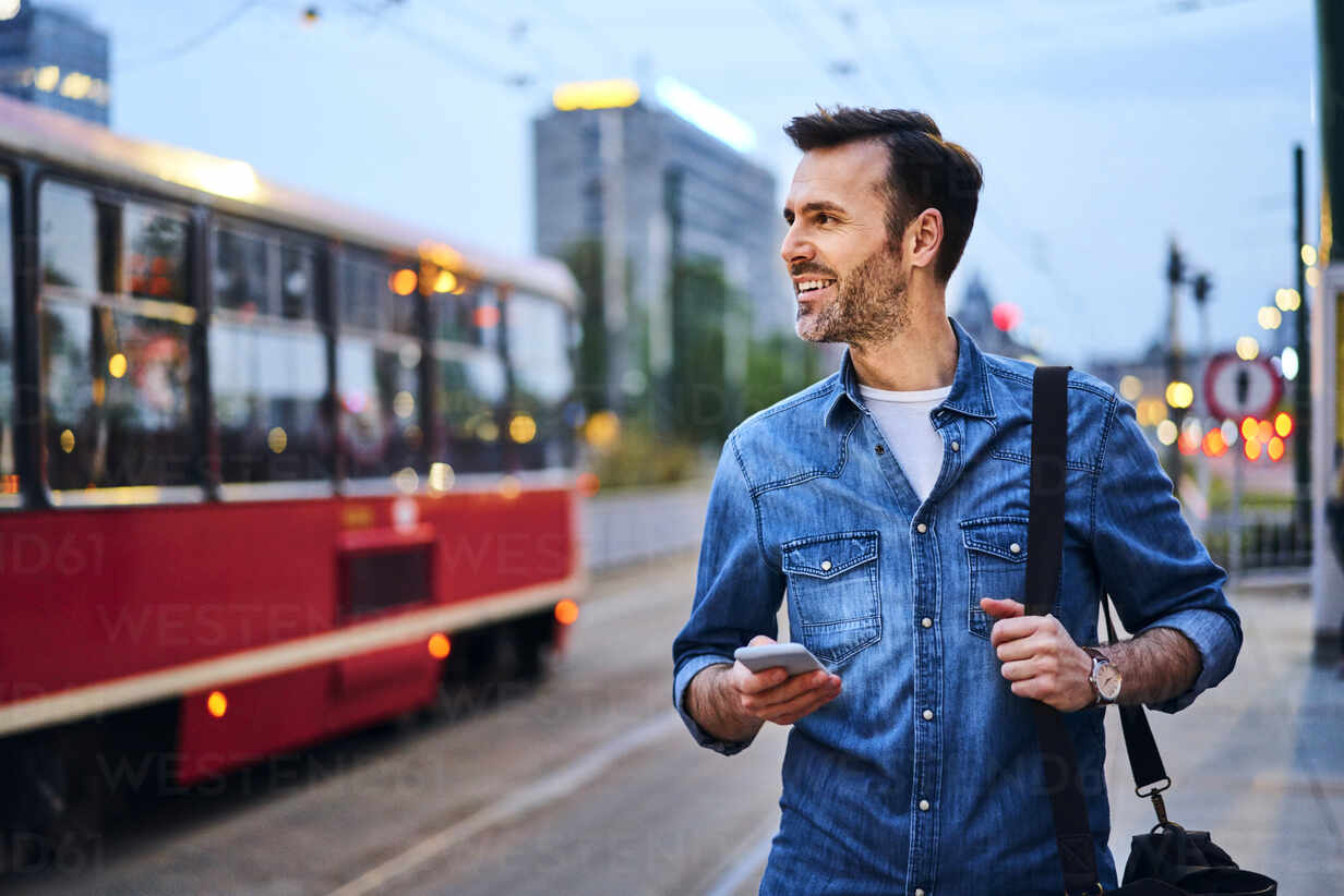 Man using smartphone while waiting for public tram in the evening - BSZF01083 - Bartek Szewczyk/Westend61