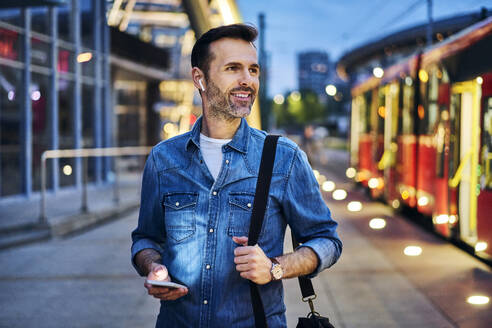 Man listening to music while waiting for tram during evening commute after work - BSZF01089