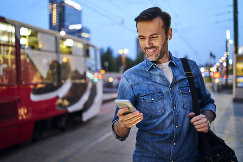 Man using smartphone and listening to music while standing at tram stop in the evening - BSZF01092