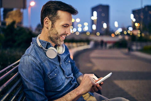 Smiling man using his smartphone while sitting on a bench in the evening - BSZF01101