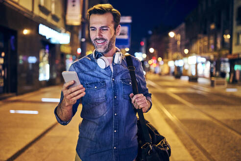 Smiling man using his smartphone in the city at night - BSZF01104