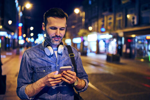 Smiling man using his smartphone in the city at night while waiting for the tram - BSZF01107