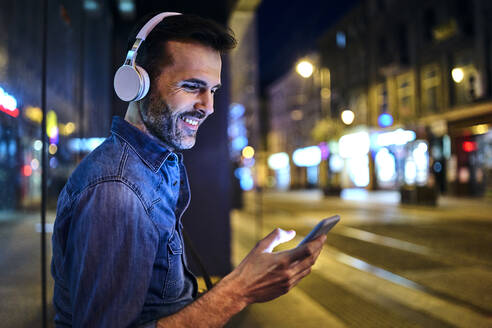 Smiling man with headphones using smartphone while waiting for night bus in the city - BSZF01110