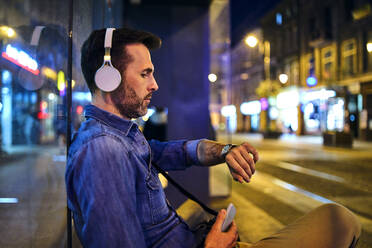 Serious man with wireless headphones waiting for night bus in the city and checking the time - BSZF01113