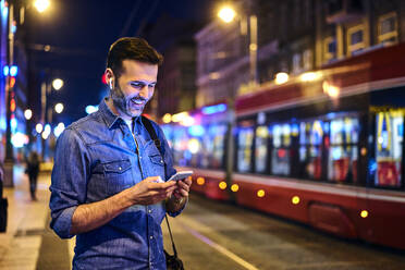 Smiling man with wireless headphones using smartphone while waiting for tram at night - BSZF01116