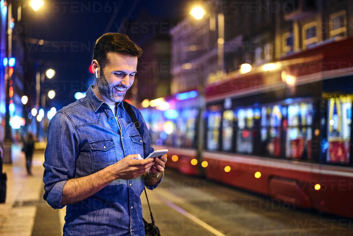 Smiling man with wireless headphones using smartphone while waiting for tram at night - BSZF01116 - Bartek Szewczyk/Westend61