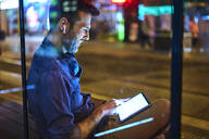 Man with headphones sitting at a station at night using his digital tablet - BSZF01119