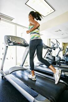Mixed race woman running on treadmill in gymnasium - BLEF09507
