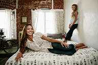 Native American mother and daughter smiling on bed - BLEF09522
