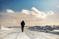 Caucasian man walking in snowy landscape - BLEF09633