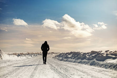 Caucasian man walking in snowy landscape - BLEF09633
