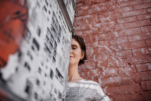 Russia, Moscow, Low angle view of woman standing by brick wall - OGF00037