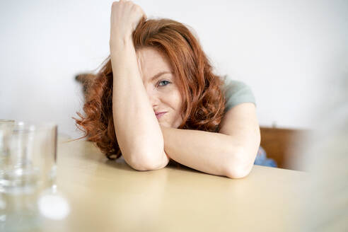 Portrait of mid adult woman leaning on table at home - DMOF00159