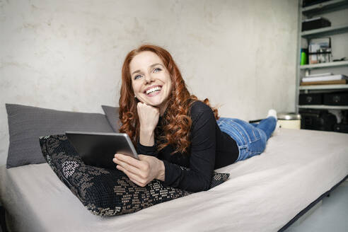 Thoughtful redhead woman with digital tablet lying on sofa while looking away at home - DMOF00171