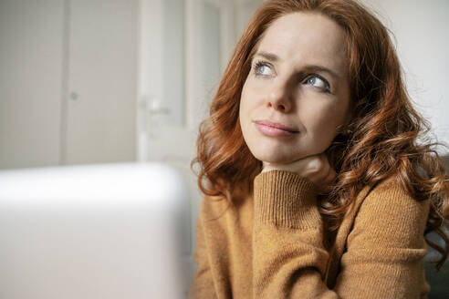 Close-up of redhead woman thinking while looking away at home - DMOF00174