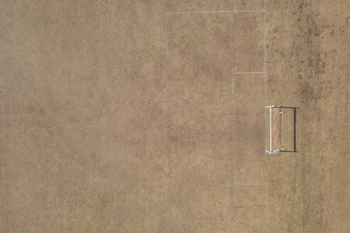 Aerial view of goal post on dry soccer field in summer during drought - MMAF01087