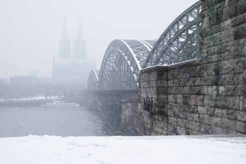 Hohenzollern Bridge over Rhine river by Cologne Cathedral during snowfall in city against sky - GWF06136