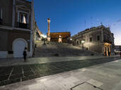 Illuminated Roman column on steps amidst buildings in Brindisi against sky at night - AMF07170