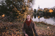 Happy woman playing with autum leaves - OGF00050
