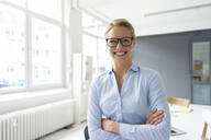 Portrait of smiling young businesswoman in office - JOSF03456