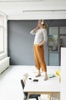 Young businesswoman listening to music with headphones standing on desk in office - JOSF03459