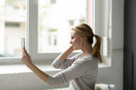 Smiling young woman holding tablet at the window - JOSF03510
