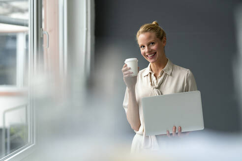 Smiling young businesswoman with laptop and takeaway coffee - JOSF03522